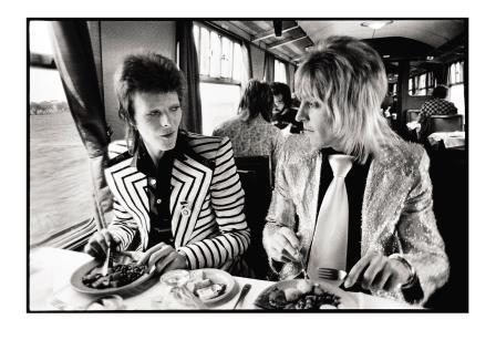 David Bowie i Mick Ronson esmorzen en un tren, una imatge signada per Mick Rock